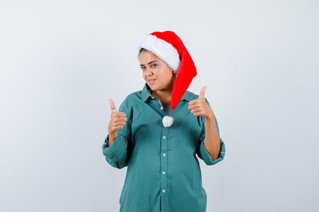 Jonge dame in kerstmuts, shirt duimen opdagen en tevreden kijken, vooraanzicht.