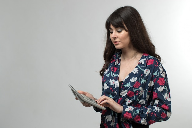 Jonge dame in ontworpen t-shirt met rekenmachine met lang haar op wit