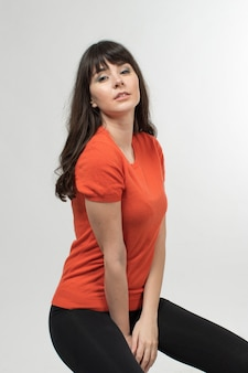 Jonge dame in ontworpen t-shirt poseren in goed humeur met lang haar op wit