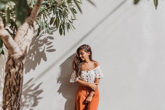 Jonge dame in oranje broek en blouse met blote schouders glimlacht zoet, leunend op witte muur onder boom