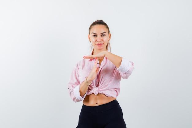 Jonge dame in overhemd, broek die het gebaar van de tijdonderbreking toont en op zoek zelfverzekerd, vooraanzicht.