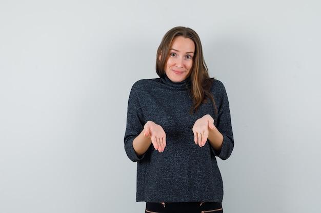 Jonge dame in overhemd die lege handpalmen toont en positief kijkt