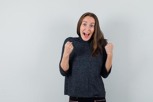 Jonge dame in overhemd die winnaargebaar toont en gek kijkt
