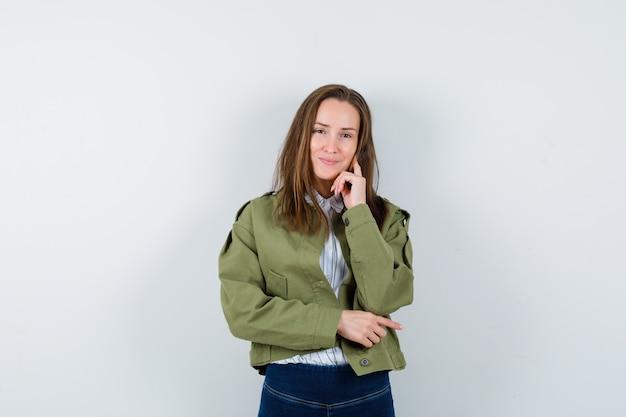Jonge dame in overhemd, jas staat in denkende houding en ziet er optimistisch uit, vooraanzicht.