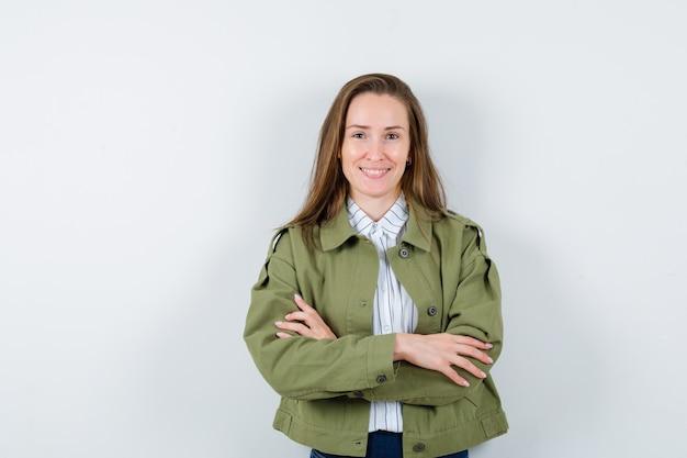 Jonge dame in overhemd, jas staat met gekruiste armen en ziet er zelfverzekerd uit, vooraanzicht.