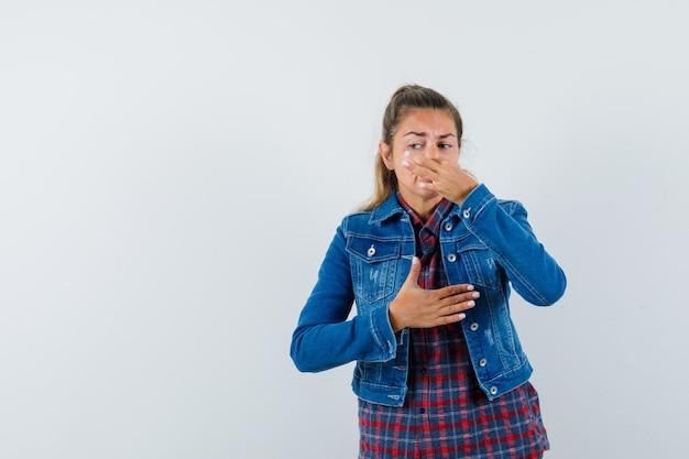 Jonge dame in overhemd, jasje die neus door slechte geur knijpt en walgt, vooraanzicht kijkt.