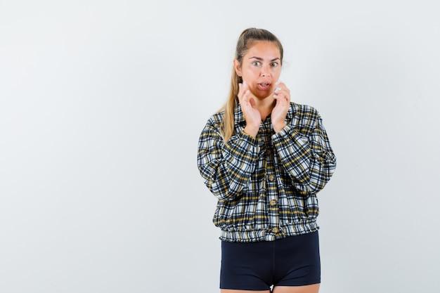 Jonge dame in overhemd, korte broek die doet alsof ze iets kleins vasthoudt en peinzend kijkt, vooraanzicht.