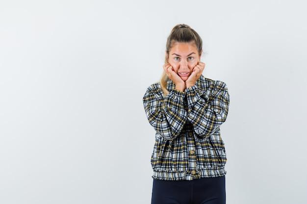 Jonge dame in overhemd, korte broek die gezicht op haar handen bedekt en er schattig uitziet, vooraanzicht.