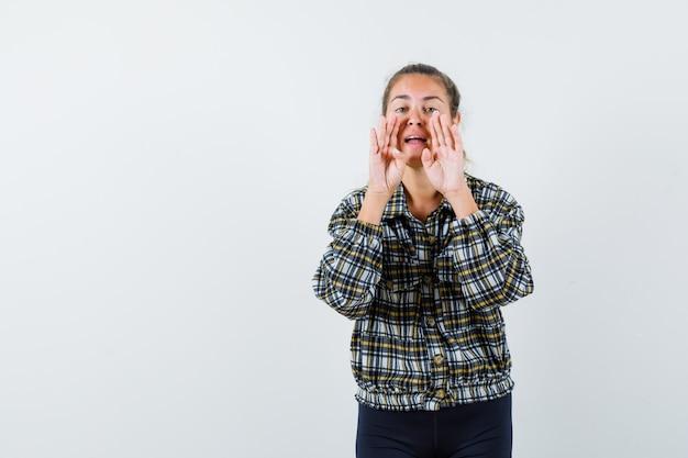 Jonge dame in overhemd, korte broek die iets schreeuwt of aankondigt, vooraanzicht.