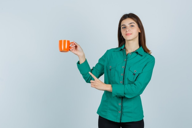 Jonge dame in overhemd met oranje kopje thee, wijzend op de linkerbovenhoek en kijkt zelfverzekerd, vooraanzicht.