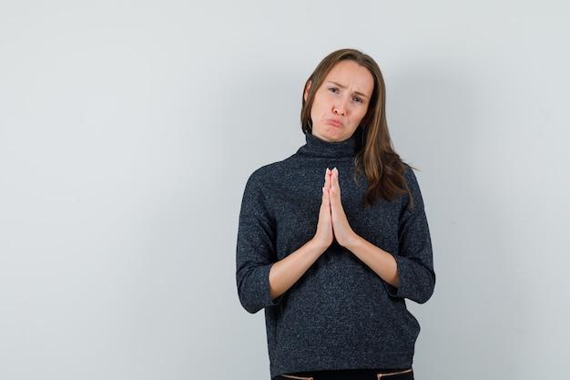 Jonge dame in overhemd namaste gebaar tonen en nederig kijken