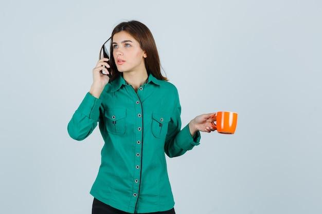 Jonge dame in overhemd oranje kopje thee houden, praten over de mobiele telefoon en op zoek voorzichtig, vooraanzicht.
