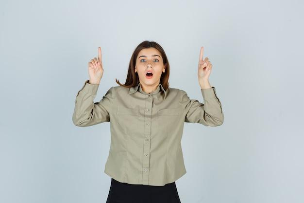 Jonge dame in overhemd, rok die omhoog wijst en perplex kijkt