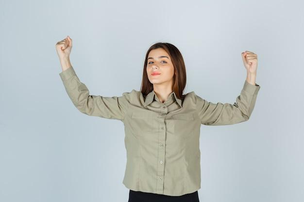 Jonge dame in overhemd, rok die winnaargebaar toont en gelukkig kijkt, vooraanzicht.