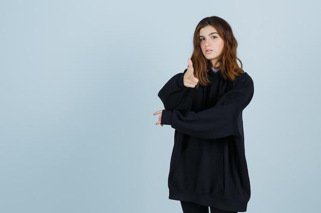 Jonge dame in oversized hoodie, broek die camera richt en er zelfverzekerd uitziet, vooraanzicht.