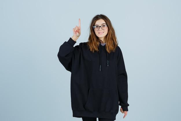 Jonge dame in oversized hoodie, broek die op en neer wijst en er gelukkig uitziet, vooraanzicht.