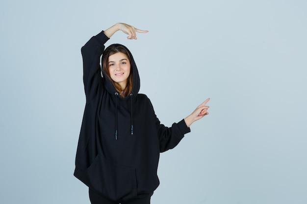 Jonge dame in oversized hoodie, broek die opzij wijst en er gelukkig uitziet, vooraanzicht.
