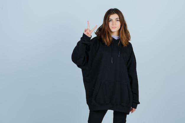 Jonge dame in oversized hoodie, broek met overwinningsteken en op zoek naar geluk, vooraanzicht.