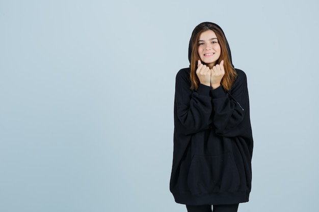 Jonge dame in oversized hoodie, broek met vuisten in de buurt van gezicht en op zoek schattig, vooraanzicht.