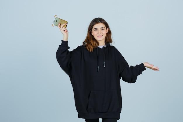 Jonge dame in oversized hoodie, broek spreidt de handpalmen opzij terwijl ze de telefoon vasthoudt en er gelukkig uitziet, vooraanzicht.