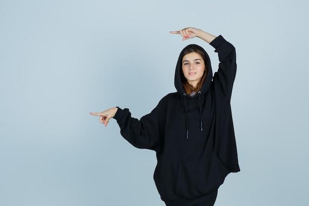 Jonge dame in oversized hoodie, broek wijst naar de linkerkant en ziet er zelfverzekerd uit, vooraanzicht.
