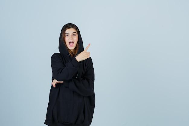 Jonge dame in oversized hoodie, broek wijst naar de rechterbovenhoek en kijkt verbaasd, vooraanzicht.