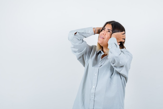 Jonge dame in oversized shirt hand in hand op oren en gefocust, vooraanzicht.