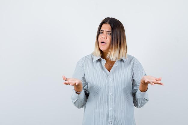 Jonge dame in oversized shirt spreidt handpalmen in een onwetend gebaar en ziet er serieus uit, vooraanzicht.