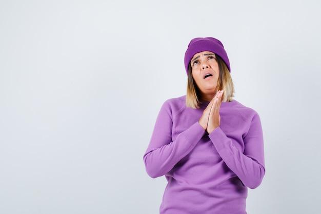 Jonge dame in paarse trui, muts met handen in gebedsgebaar en hoopvol kijkend, vooraanzicht.