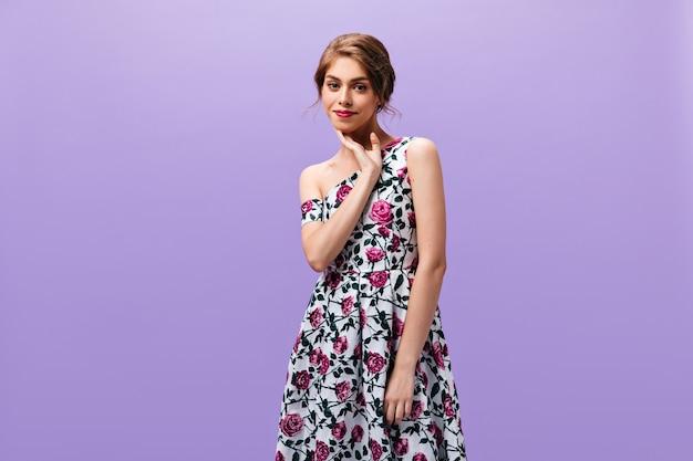 Jonge dame in prachtige jurk vormt op geïsoleerde achtergrond. prachtige vrouw met rode lippenstift in modieuze kleding op zoek naar camera.