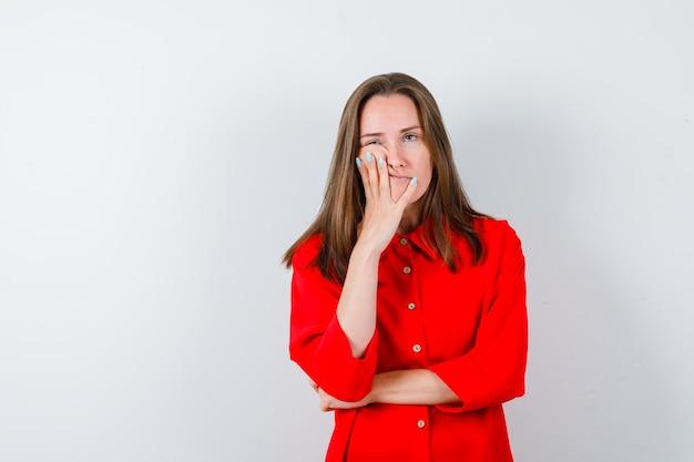 Jonge dame in rode blouse leunend op de wang en verveeld, vooraanzicht.