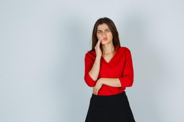 Jonge dame in rode blouse, rok die aan kiespijn lijdt en onwel kijkt