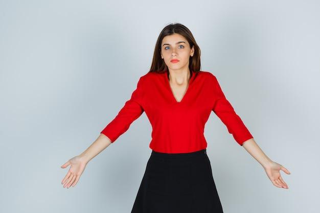 Jonge dame in rode blouse, rok die armen opzij strekt en hulpeloos kijkt