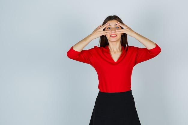 Jonge dame in rode blouse, rok die door vingers kijkt en er schattig uitziet