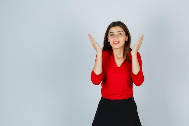 Jonge dame in rode blouse, rok die een boe-geroep speelt en er schattig uitziet
