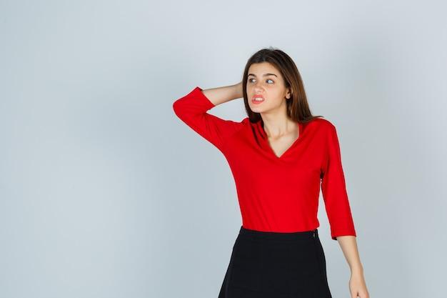 Jonge dame in rode blouse, rok die hand achter hoofd houdt en nadenkend kijkt