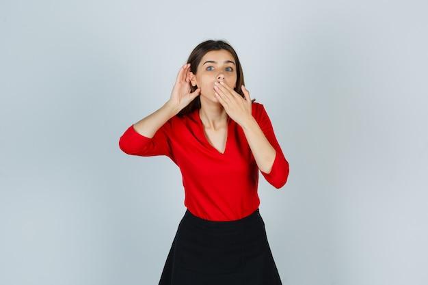 Jonge dame in rode blouse, rok die hand achter oor houdt terwijl mond wordt bedekt