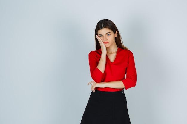 Jonge dame in rode blouse, rok die hand op wang houdt en somber kijkt