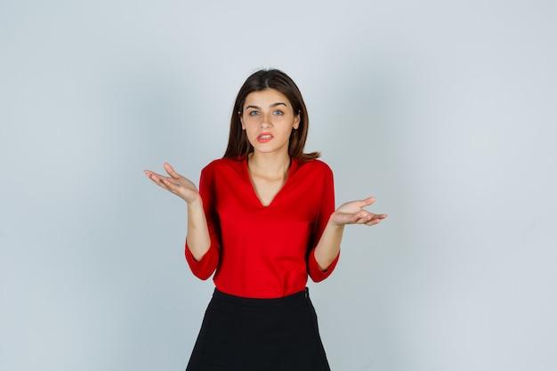 Jonge dame in rode blouse, rok die hulpeloos gebaar toont en hopeloos kijkt