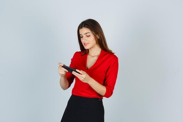 Jonge dame in rode blouse, rok die mobiele telefoon bekijkt en gelukkig kijkt