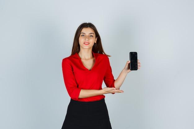 Jonge dame in rode blouse, rok die mobiele telefoon toont en zelfverzekerd kijkt