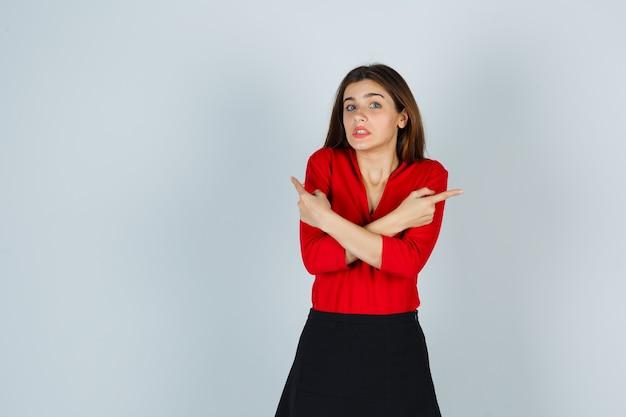 Jonge dame in rode blouse, rok die naar beide kanten wijst en aarzelend kijkt