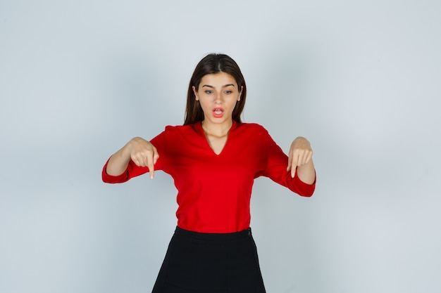 Jonge dame in rode blouse, rok die naar beneden wijst en verbaasd kijkt