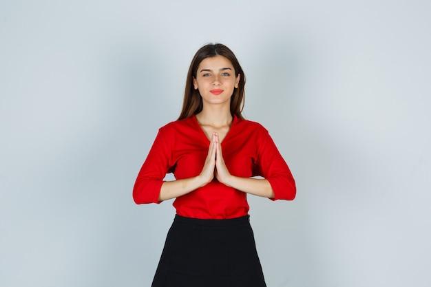 Jonge dame in rode blouse, rok die namaste-gebaar toont en vredig kijkt