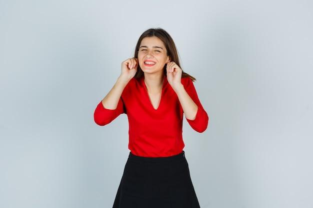 Jonge dame in rode blouse, rok die oorlellen trekt en er grappig uitziet