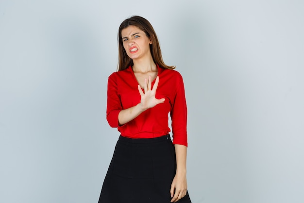 Jonge dame in rode blouse, rok die stopgebaar toont en walgt