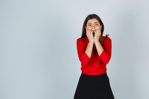 Jonge dame in rode blouse, rok die zich in bang stelt en bang kijkt