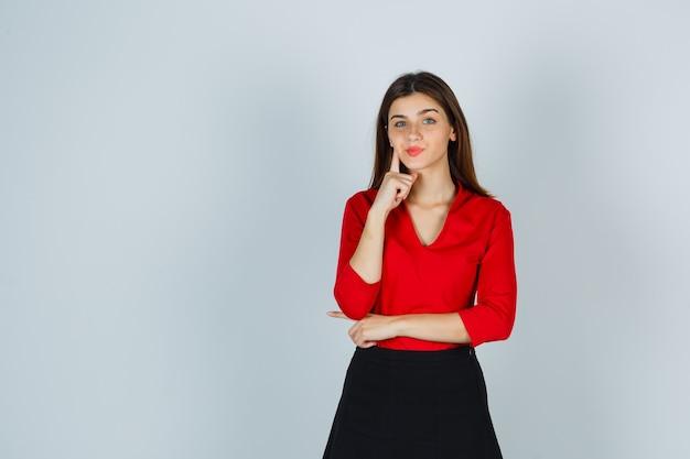 Jonge dame in rode blouse, rok die zich in denken stelt en peinzend kijkt