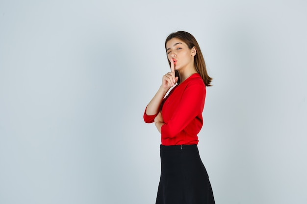 Jonge dame in rode blouse, zwarte rok die stilte gebaar toont en er schattig uitziet