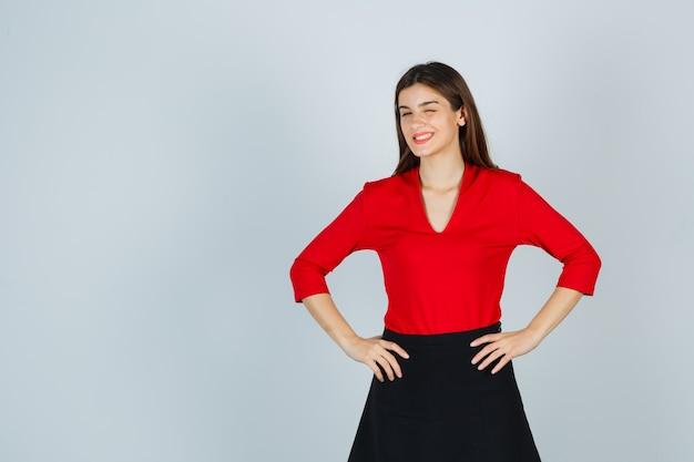 Jonge dame in rode blouse, zwarte rok hand in hand op de heupen, knipogen en er schattig uitzien